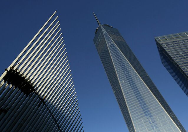 One World Trade Center stands between the transportation hub, left, still under construction, and 7 World Trade Center, right, Monday,