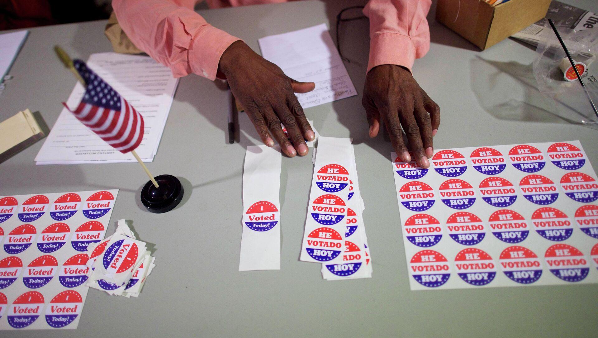 A majority inspector arranges 'I Voted Today!' stickers at registration on U.S. midterm election day morning at Holmes School Senior Center in Philadelphia, Pennsylvania, November 4, 2014 - Sputnik International, 1920, 28.07.2021