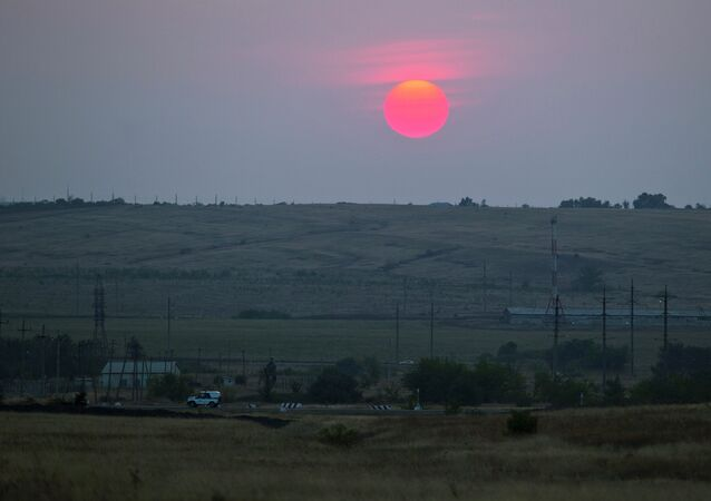A police car moves in an emptied field where trucks of the aid convoy were parked about 28 kilometers (17 miles) from the Ukrainian border, near Kamensk-Shakhtinsky, Rostov-on-Don region, Russia, during sunset at Friday, Aug. 22, 2014