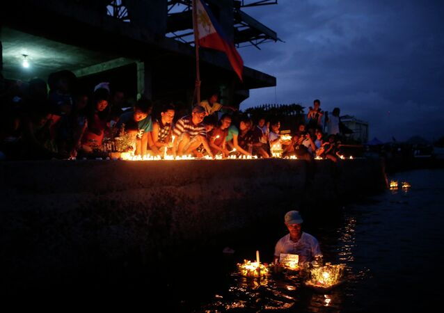 Typhoon survivors light candles to commemorate the victims who perished during the onslaught of Typhoon Haiyan a year ago in Tacloban city
