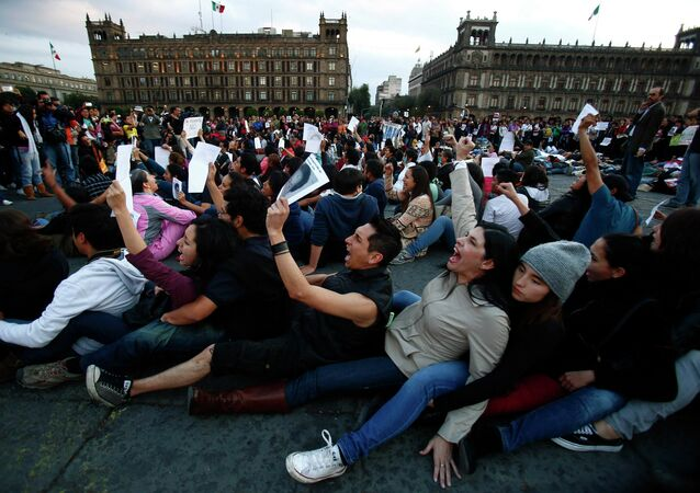 Demonstrators sit on the floor during a protest in support of the missing Ayotzinapa Teacher Training College Raul Isidro Burgos students at Zocalo square in Mexico City