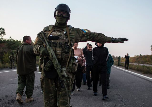 A Ukrainian soldier (C) stands guard as members of the eastern Ukrainian militia, who are prisoners-of-war (POWs), walk along a road as they wait to be exchanged, north of Donetsk, eastern Ukraine, September 28, 2014