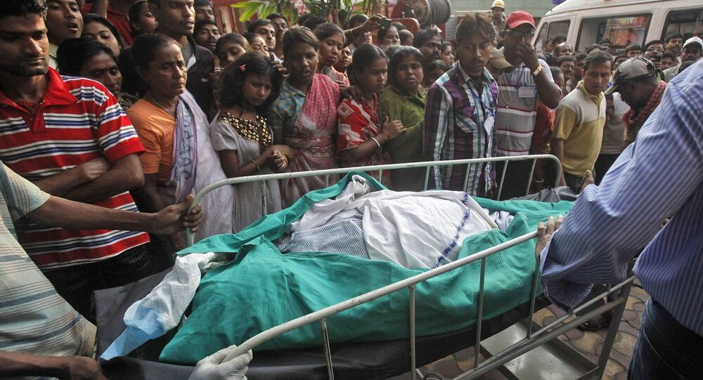 People watch as the body of a victim of a fire is wheeled towards an ambulance outside a private hospital in Kolkata, India, Friday, Dec. 9, 2011