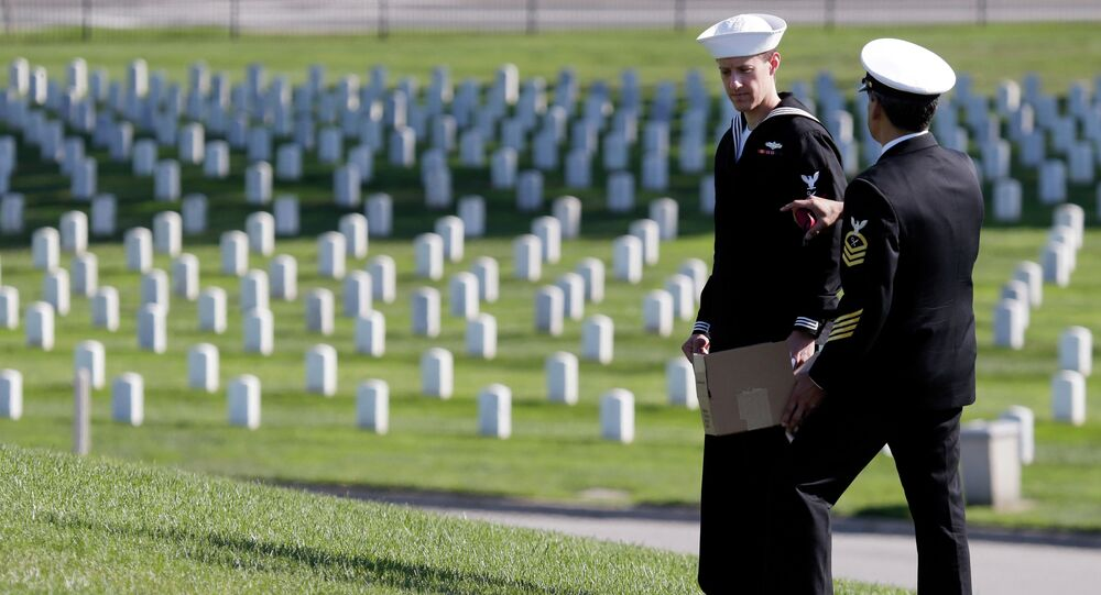 U.S. Navy reservists Michael Ohls, left, and Garbriel Garcia chat after serving as honor detail for a war veteran's burial ceremony at Golden Gate National Cemetery on Monday, Nov. 10, 2014, in San Bruno