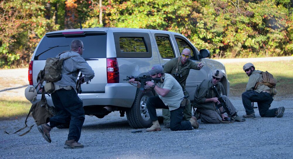 Members of the US Diplomatic Security Service take cover and return fire during a simulated ambush on a motorcade during a High Threat training program held at a mock town named Erehwon, nowhere spelled backwards, on a rural Virginia military base, Thursday, Oct. 9, 2014