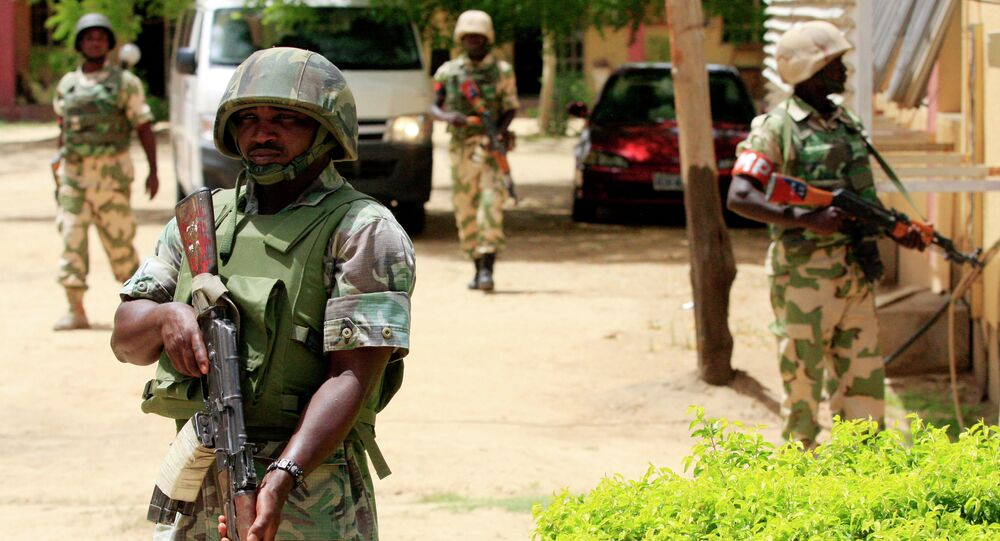 In this Thursday, June 6, 2013 file photo Nigerian soldiers stand guard at the offices of the state-run Nigerian Television Authority in Maiduguri, Nigeria