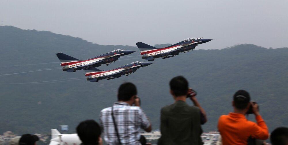 Посетители фотографирают самолеты во время авиасалоне в Чжухае
