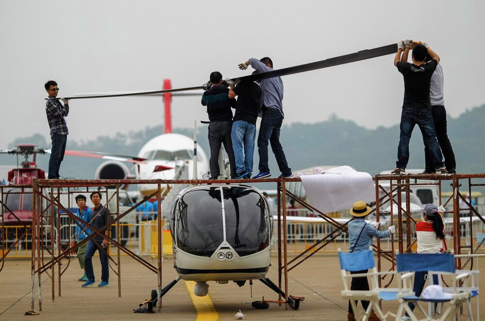Рабочие устанавливают пропеллер на вертолет перед началом Китайского международного авиасалона