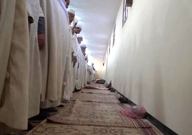 In this image taken Friday Feb. 7, 2014 Muslims pray in honor of Azzedine Babaousmail, a Berber who died of his wounds on Thursday in Algeria's desert city of Ghardaia, southern Algeria, bringing to five the number killed during weeks of violence between two rival communities in Ghardaia