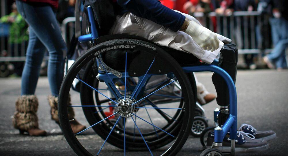 Senior Airman, Brian Kolfage Jr. rolls in his wheelchair with his wife Ashley (L)