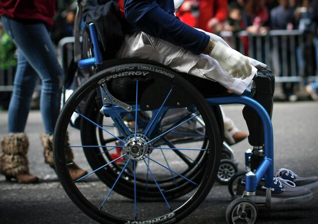 Senior Airman, Brian Kolfage Jr. rolls in his wheelchair with his wife Ashley (L)