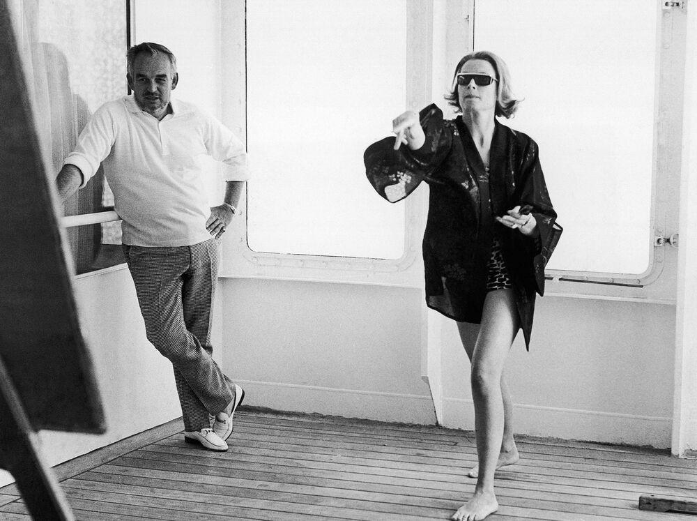 Принц Монако Ренье III наблюдает за тем, как его жена Грейс Келли играет в дротики