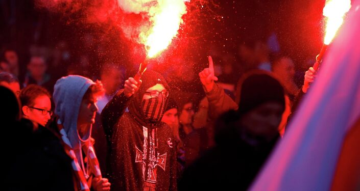 A protester holds a flare as several hundred masked men broke away from a far-right march and threw stones and flares at lines of riot police in Warsaw November 11, 2014