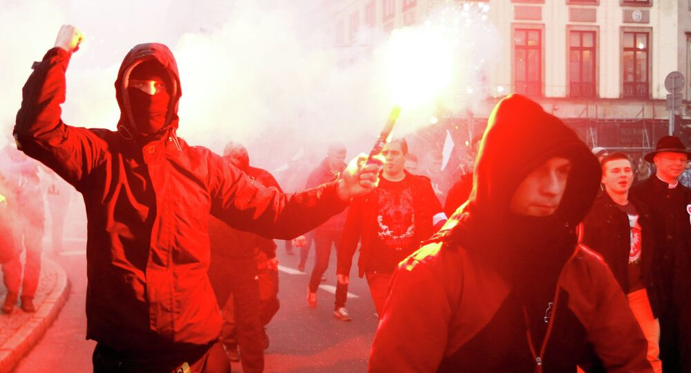 A far-right protester holds a flare during the annual far-right rally, which coincides with Poland's National Independence Day in Warsaw November 11, 2014