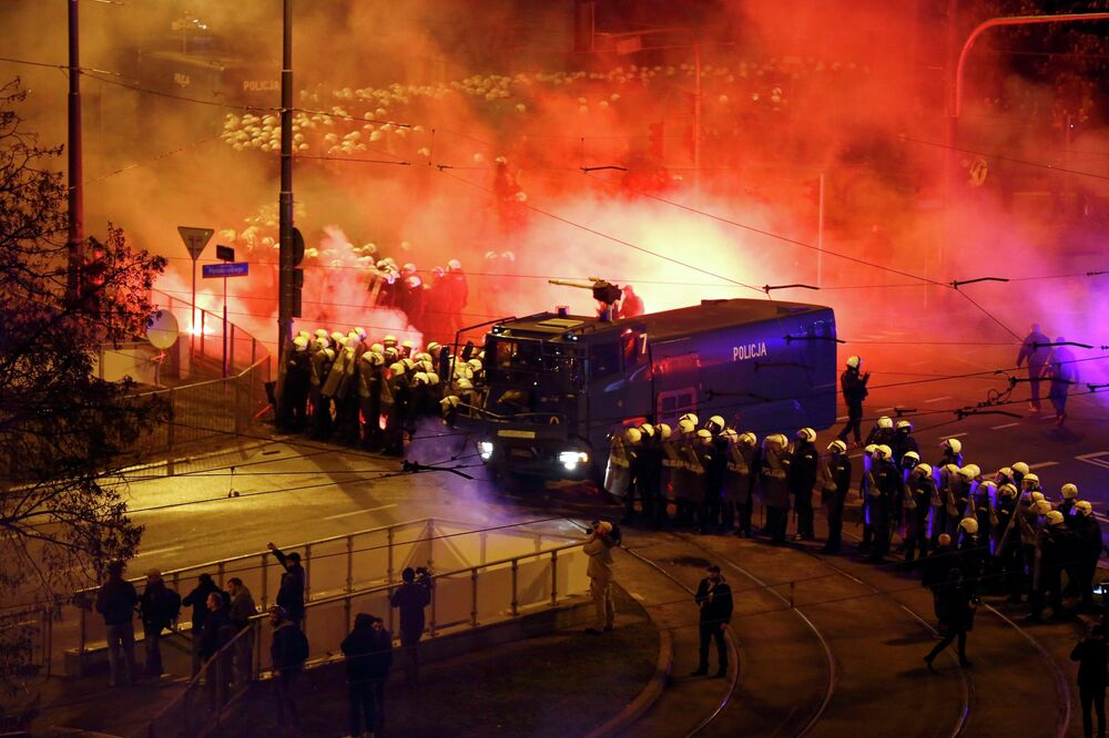 Riot policemen stand beside a water cannon as several hundred masked men who broke away from a far-right march threw stones and flares in Warsaw November 11, 2014