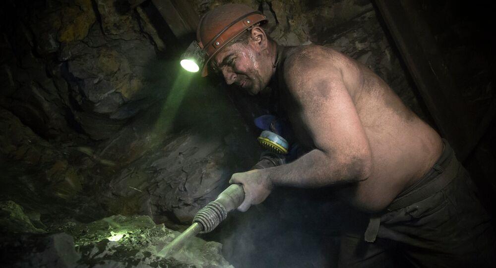 In this photo taken Thursday, October 30, 2014, miner Vitaly Khristich uses a jackhammer at the Chelyuskintsev coal mine in the city of Donetsk, eastern Ukraine