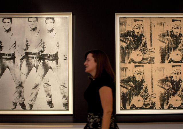 A woman walks between Triple Elvis and Four Marlons by Andy Warhol during a media preview at Christie's auction house in New York, October 31, 2014