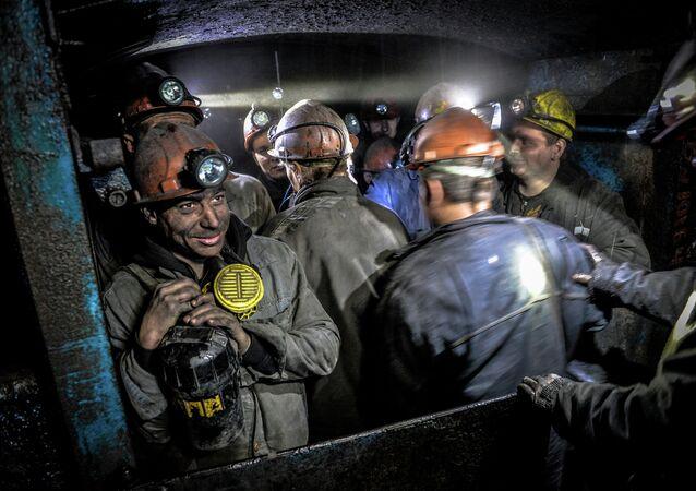 Miners leave the mine cage inside the Glubokaya mine, Shakhtyorsk