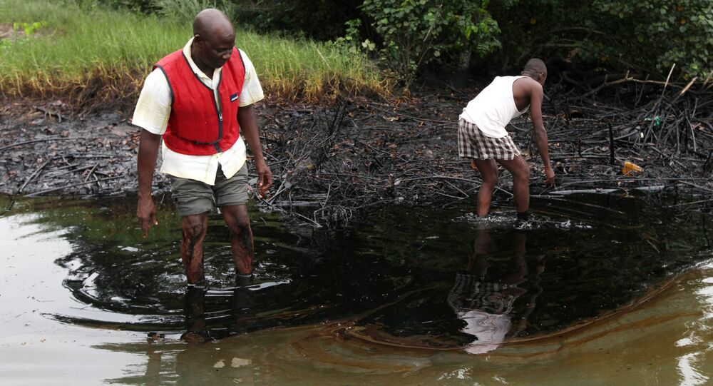 In this June 20, 2010 file photo, men walk in an oil slick covering a creek near Bodo City in the oil-rich Niger Delta region of Nigeria