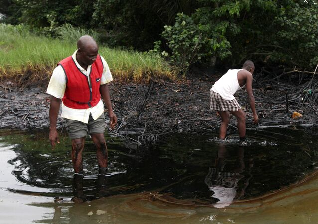 In this June 20, 2010 file photo, men walk in an oil slick covering a creek near Bodo City in the oil-rich Niger Delta region of Nigeria