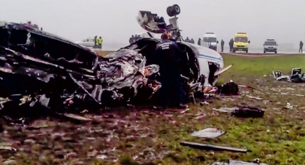 In this image made from video provided by Russian State Television Rossiya, investigators works at the wreckage of a private jet which collided with a snowplow at Vnukovo airport in Moscow, Tuesday, Oct. 21, 2014