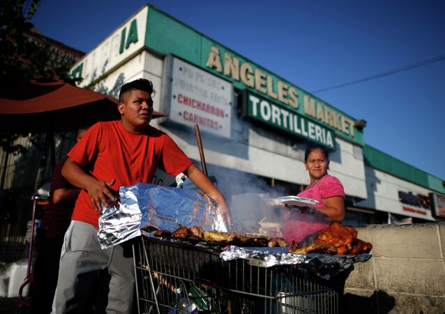 A man cooks meat in a shopping cart in the Westlake area of Los Angeles, home to many Mexican and Central American migrants, California