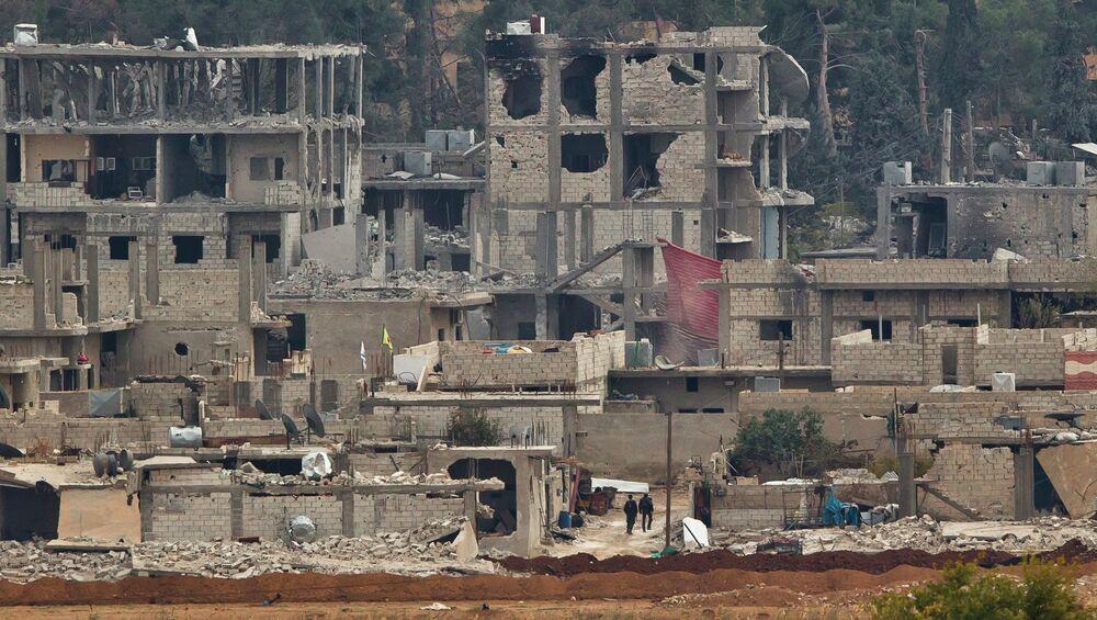 Kurdish fighters walk between damaged buildings