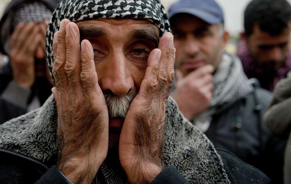 Kurds pray during a religious service