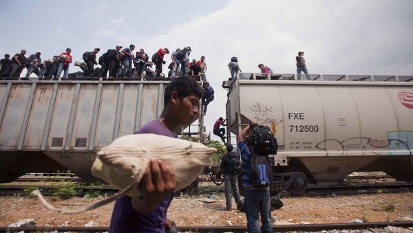 Migrants coming from Central America climb off a train during their journey toward the U.S.-Mexico border in Ixtepec, Mexico, Monday, April 29, 2013 - Sputnik International