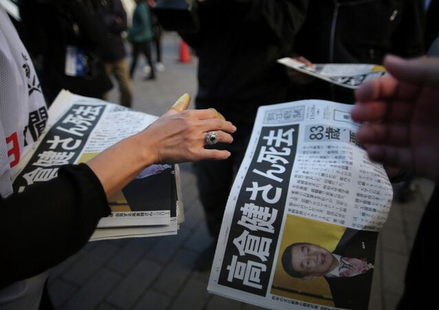 A worker, bottom, distributes an extra edition of a newspaper with front page featuring an obituary notice of acclaimed Japanese film star Ken Takakura at Shimbashi Station in Tokyo, Tuesday, Nov. 18, 2014