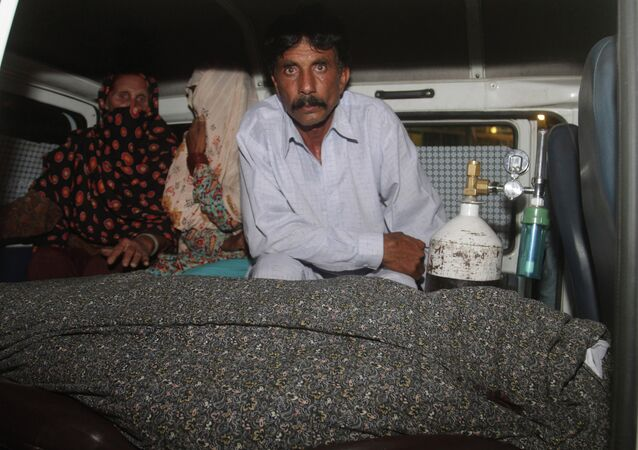Mohammad Iqbal, right, husband of Farzana Parveen, 25, sits in an ambulance next to the body of his pregnant wife who was stoned to death by her own family, in Lahore, Pakistan, Tuesday, May 27, 2014