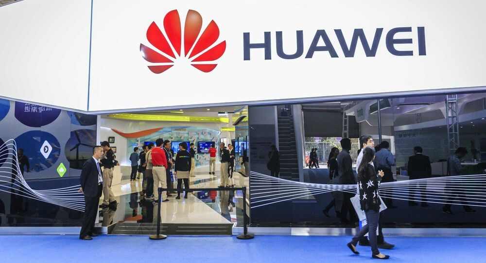 Visitors walk past the stand of Huawei during PT/EXPO COMM CHINA 2014 in Beijing, China, 27 September 2014