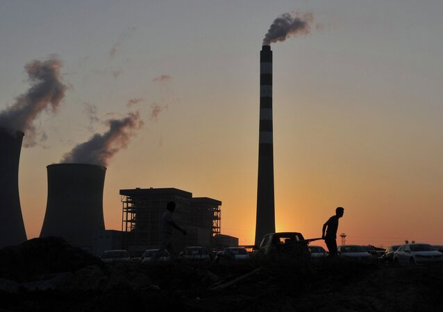 A worker pulls a cart in front of the smoking chimneys of a power plant