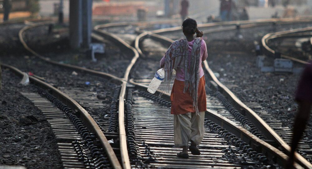 An Indian woman walks after defecating on a railway track, on World Toilet Day in Gauhati, India, Wednesday, Nov. 19 2014
