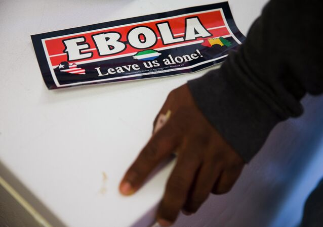 An Ebola bumper sticker sits next to Sierra Leone immigrant Mamud Jalloh's hand Wednesday, Oct. 8, 2014, in Philadelphia