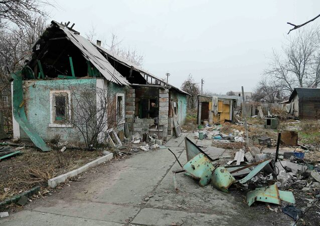 A man enters a destroyed house in the Spartak area near Sergey Prokofiev International Airport in Donetsk November 18, 2014