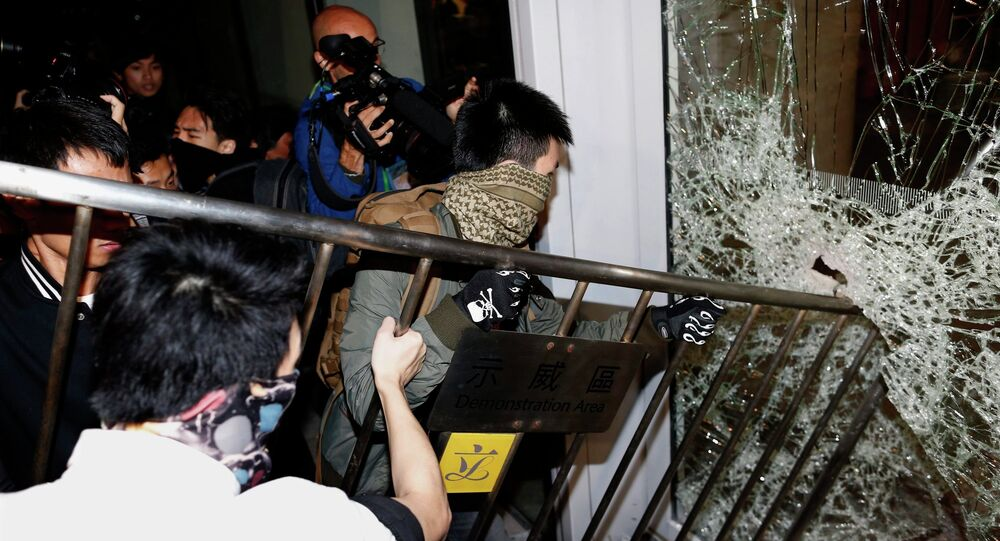 Masked pro-democracy protesters try to break with a fence a glass window of the Legislative Council in Hong Kong early November 19, 2014