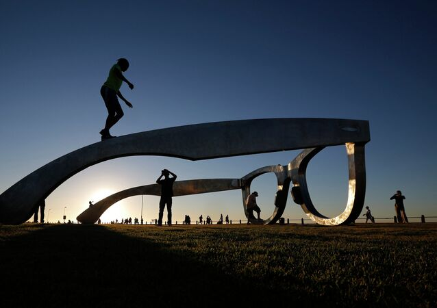 Children play under a sculpture in the form of a giant pair of spectacles on Cape Town's Sea Point Promenade, November 18, 2014