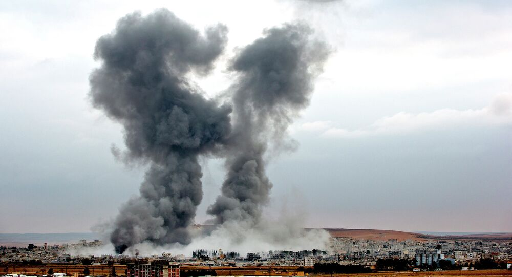 Smoke rises from the Syrian city of Kobani, following airstrikes by the US led coalition, seen from a hilltop outside Suruc, on the Turkey-Syria border Monday, Nov. 17, 2014