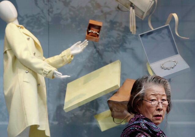 A woman walks past a display window of a luxury store