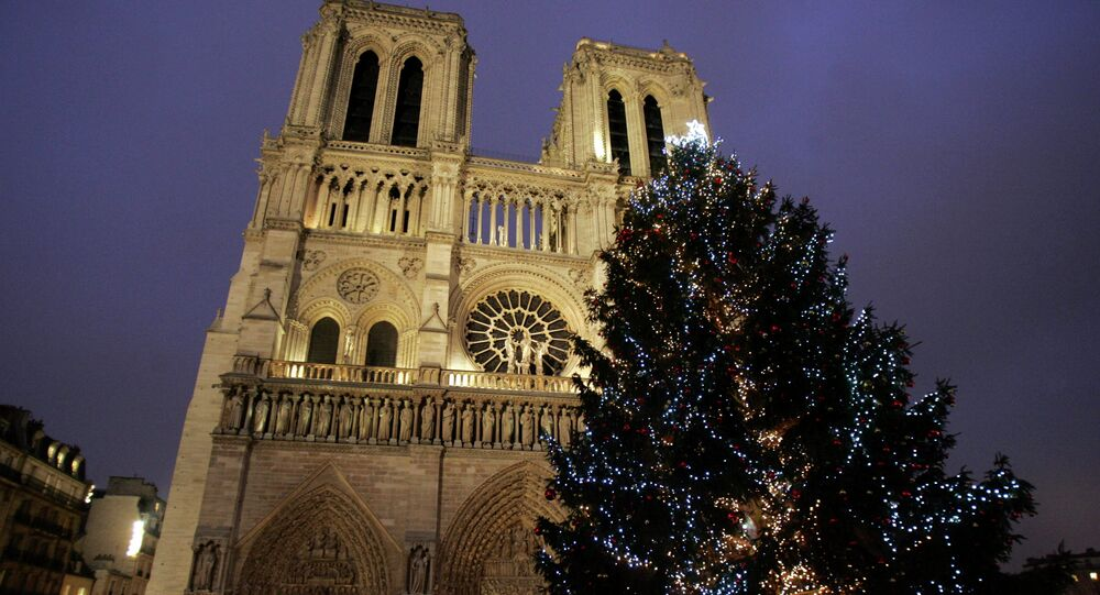 A Christmas tree is seen in front of the Notre Dame cathedral a few hours before the midnight mass, in Paris, Wednesday, Dec. 24, 2008.