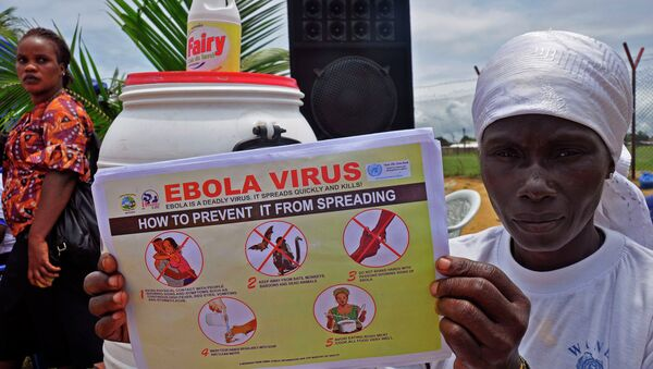 A Liberian woman holds up a pamphlet with guidance on how to prevent the Ebola virus from spreading, in the city of Monrovia, Liberia. - Sputnik International