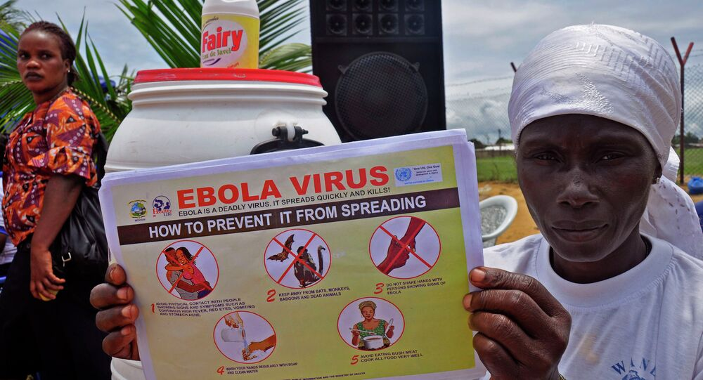 A Liberian woman holds up a pamphlet with guidance on how to prevent the Ebola virus from spreading, in the city of Monrovia, Liberia.