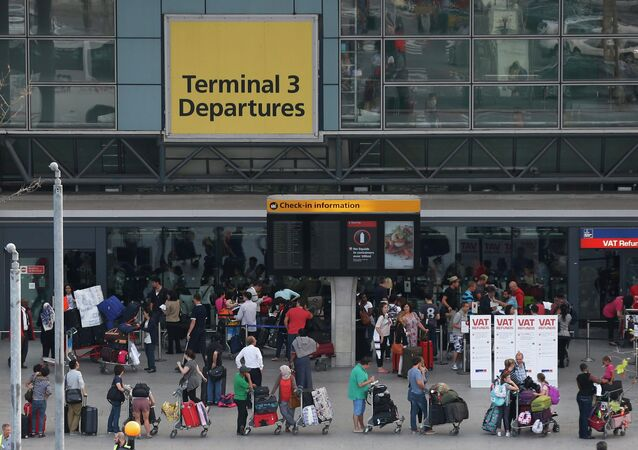 Passengers queue outside Terminal 3 at Heathrow Airport in London