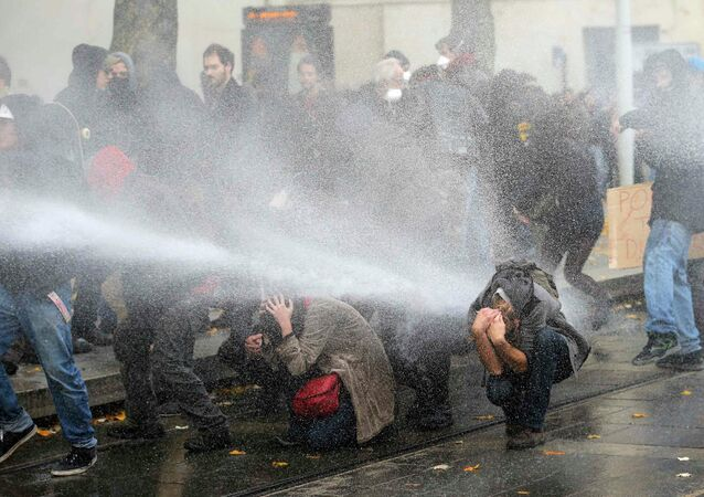 Protestors protect themselves from water canon used by French riot police as the attend a protest demonstration against police brutality in Nantes, western France