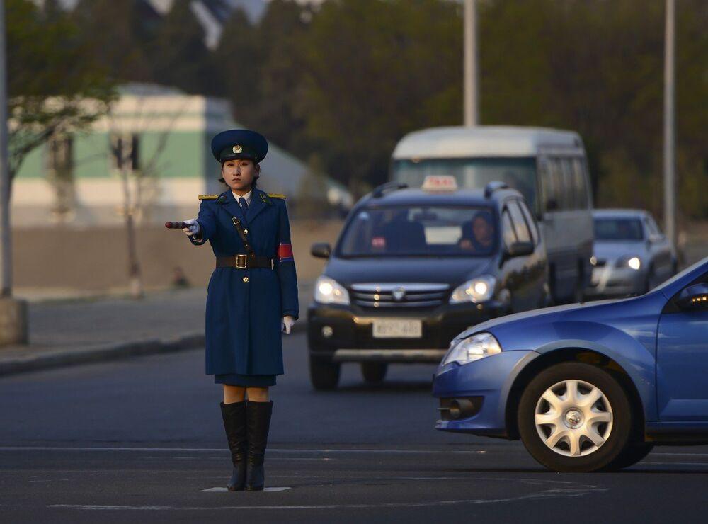 Pyongyang, North Korea: A traffic policewoman directs cars.