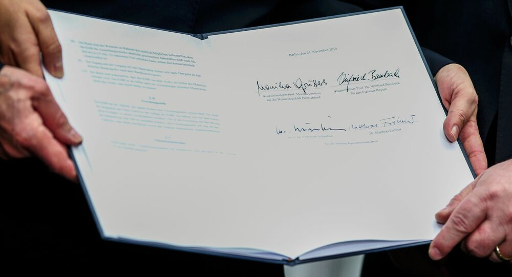 Christoph Schaeublin of the Bern Art Museum, Federal Government Commissioner for Culture Monika Gruetters and Bavaria's Justice Minister Winfried Bausback hold the signed contract on the collection from the late Cornelius Gurlitt in Berlin