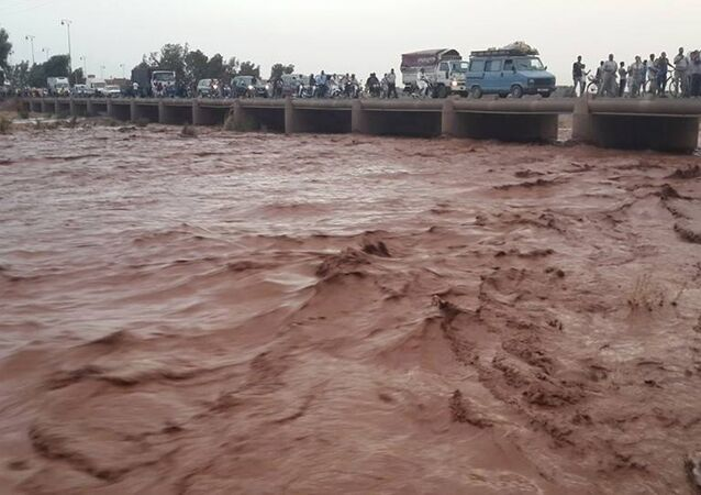 This image taken with a mobile phone shows residents of Guelmim, south western Morocco, crossing a bridge over floodwaters