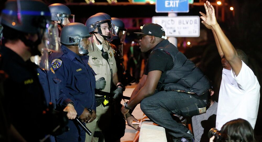 A protester faces off against a line of police on the 110 freeway during a demonstration in Los Angeles, California following the grand jury decision in the shooting of Michael Brown in Ferguson