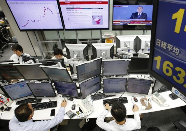Money traders work as screens show Scotland's referendum results at a foreign exchange dealing company in Tokyo